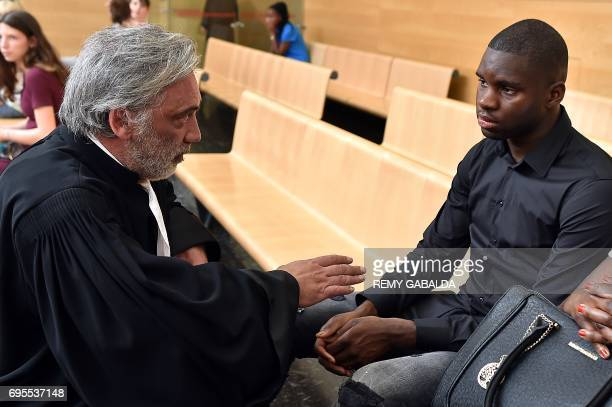 Toulouse football player Odsonne Edouard speaks with his lawyer Pierre Le bonjour prior to his hearing for 'armsbased violence' on June 13 2017 at...