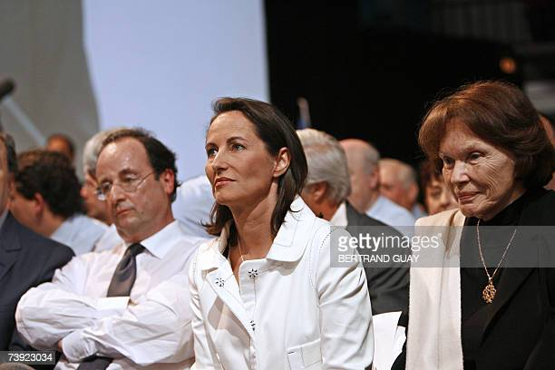 French socialist party presidential candidate Segolene Royal listens to a speech next to French Socialist Party's Prime Secretary Francois Hollande...