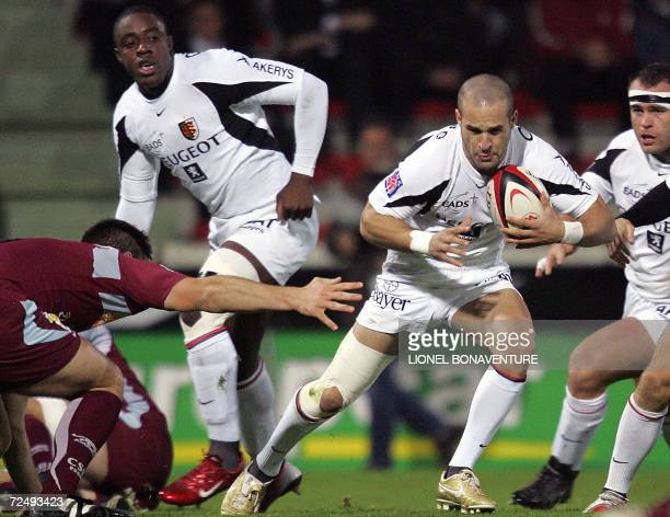 Stade Toulousain's' scrum half Frederic Michalak vies with Bourgoin's prop Pablo Cardinali as Stade toulousain's flanker Yannick Nyanga look on...
