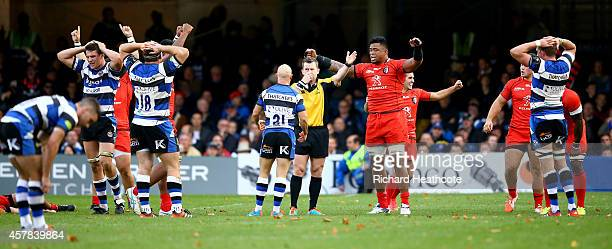 Toulouse players celebrate and Bath players look dejected at the final whistle during the European Rugby Champions Cup match between Bath Rugby and...