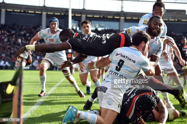 Toulouse's flanker Yacouba Camara jumps over Racing's players to score a try during the French Top 14 rugby union match between Stade Toulousain and...