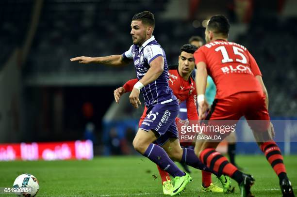 Toulouse's forward Andy Delort outruns Rennes' midfielder Benjamin Andre and Rennes' defender Ramy Bensebaini during the French L1 football match...