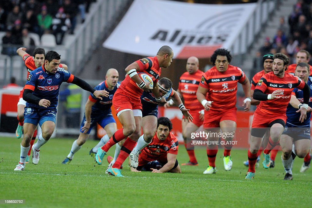 Toulouse's French centre Gaël Fickou (C) passes the ball during the French Top 14 rugby union match Grenoble (FCG) vs Stade Toulousain (ST) on December 22, 2012 at the Stade des Alpes in Grenoble AFP PHOTO / Jean Pierre Clatot