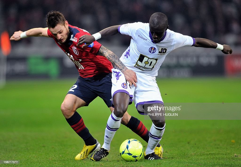 Toulouse's French defender Cheikh M'bengue (R) vies with Lille's French midfielder Mathieu Debuchy during the French L1 football match Lille vs Toulouse on December 11, 2012 at the Grand Stade Stadium in Villeneuve d'Ascq. AFP PHOTO / PHILIPPE HUGUEN