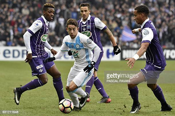 Toulouse's French defender Christopher Jullien and Toulouse's Brazilian midfielder Somalia vie with Olympique de Marseille's French midfielder Maxime...