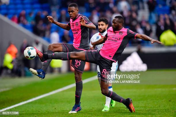 Toulouse's French defender Issa Diop and Toulouse's Malian midfielder Tongo Doumbia vie for the ball with Lyon's French midfielder Nabil Fekir during...