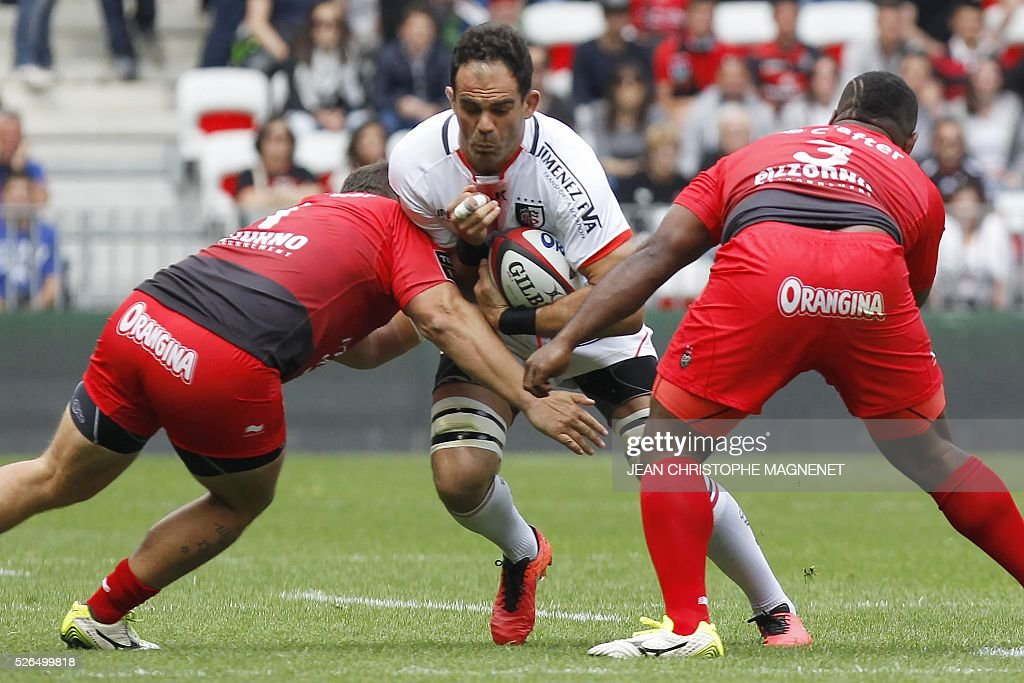 Toulouse's French flanker Gregory Lamboley (C) is tackled during the French Top 14 rugby union match Toulon vs Toulouse on April 30, 2016 at the 'Allianz Riviera' stadium in Nice, southeastern France.