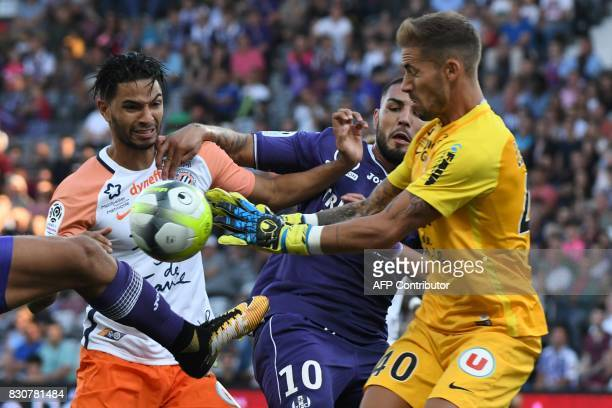 Toulouse's French forward Andy Delort fights for the ball with Montpellier's Portuguese defender Pedro Mendes and Montpellier's French goalkeeper...