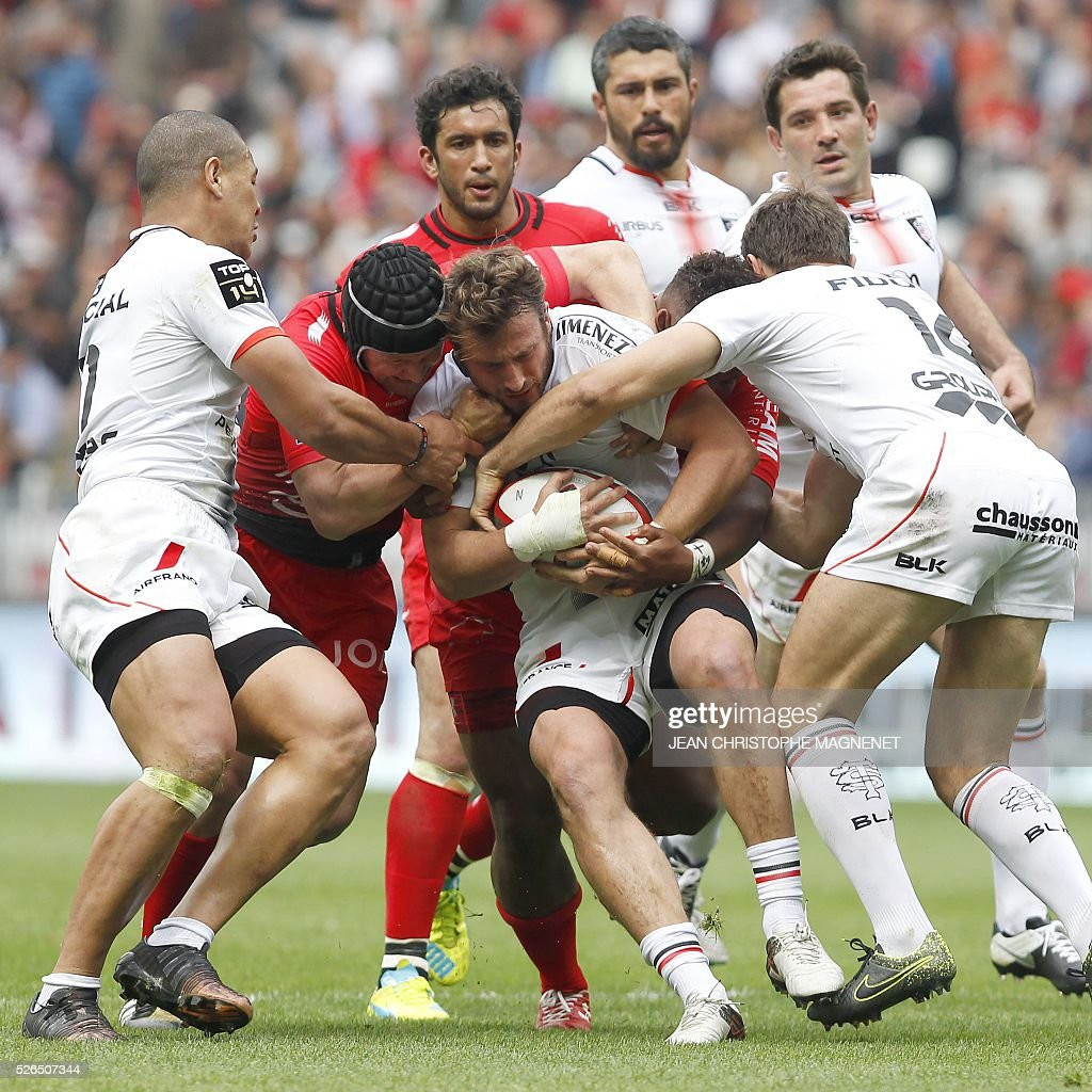 Toulouse's French fullback Maxime Medard (C) is tackled during the French Top 14 rugby union match Toulon vs Toulouse on April 30, 2016 at the 'Allianz Riviera' stadium in Nice, southeastern France.