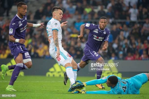 Toulouse's French goalkeeper Alban Lafont grabs the ball in the feet of Olympique de Marseille's Argentinian forward Lucas Ocampos during the French...