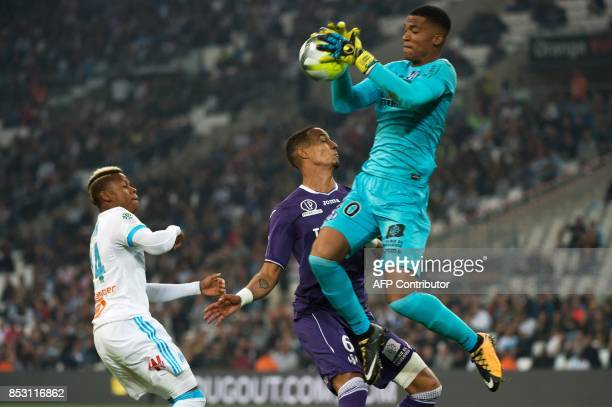 Toulouse's French goalkeeper Alban Lafont makes a save next to Toulouse's French defender Christopher Jullien and Olympique de Marseille's...
