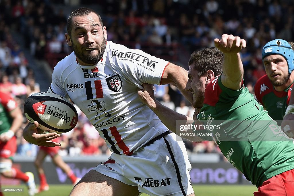 Toulouse's French scrum-half <a gi-track='captionPersonalityLinkClicked' href=/galleries/search?phrase=Jean-Marc+Doussain&family=editorial&specificpeople=7427141 ng-click='$event.stopPropagation()'>Jean-Marc Doussain</a> (L) breaks away from Bayonne's players during the French Top 14 rugby union match Toulouse against Bayonne on April 11, 2015 at the Ernest Wallon Stadium in Toulouse, southern France.
