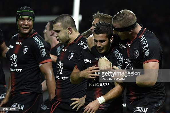 Toulouse's French scrumhalf Sebastien Bezy celebrates with teammates after scoring during the French Top 14 rugby union match between Toulouse and...