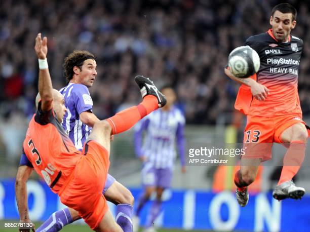 Toulouse's midfielder Gilles Siriex vies with Lyon's defenders Cris and Anthony Reveillere during the French L1 football match Toulouse vs Lyon on...