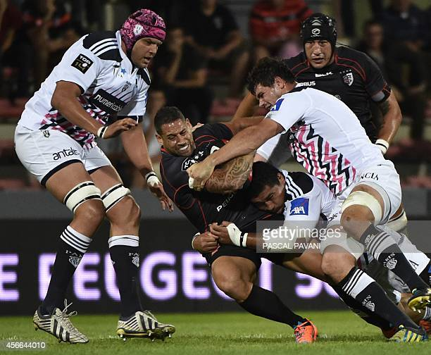 Toulouse's New Zelander flyhalf Luke Mc Alister is tackled by Stade Francais Paris' Samoan prop Sakaria Taulafo next to by Stade Francais Paris'...