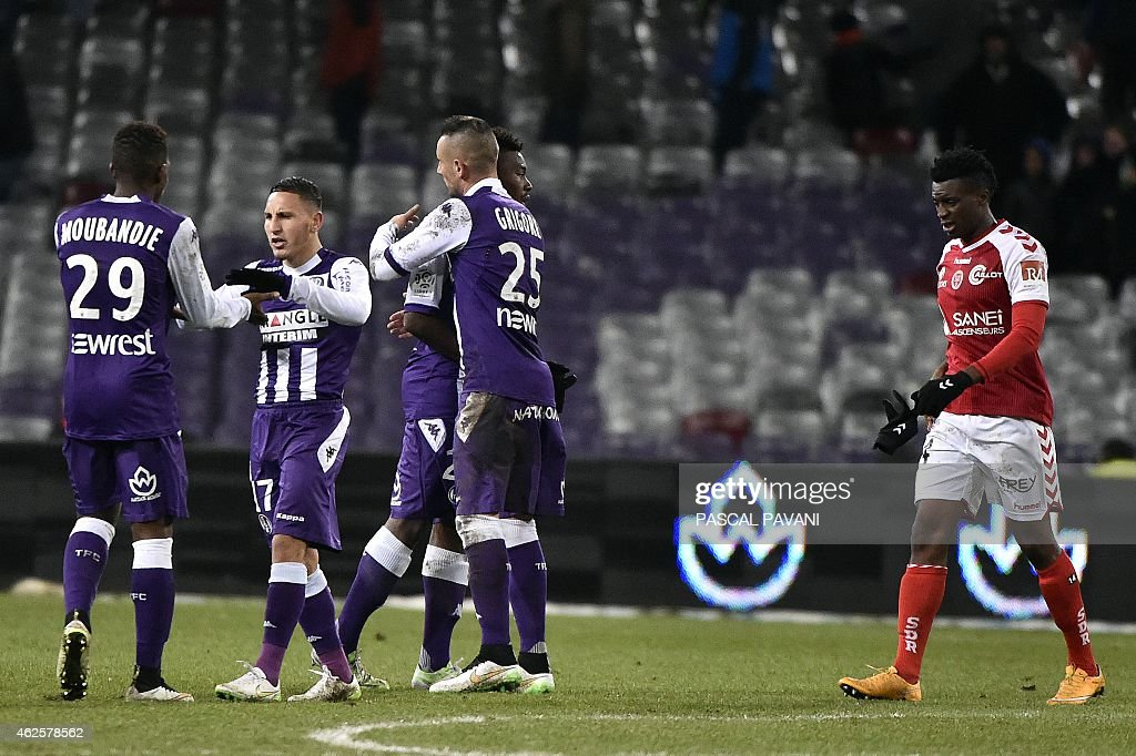 Toulouse's players celebrates (L) as Reims' Cameroonian forward <a gi-track='captionPersonalityLinkClicked' href=/galleries/search?phrase=Benjamin+Moukandjo&family=editorial&specificpeople=7470600 ng-click='$event.stopPropagation()'>Benjamin Moukandjo</a> reacts at the end of the French L1 football match Toulouse against Reims on January 31, 2015 at the Municipal Stadium in Toulouse.