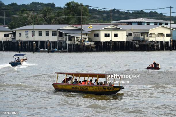 A tour boat brings passengers around Kampung Ayer in Bandar Seri Begawan on October 4 2017 Brunei will mark its Sultan's Hassanal Bolkiah 50th...