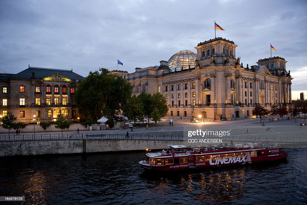 A tour boat passes the Reichstag (R), the building housing the German lower house of parliament and the Jakob Kaisers haus (L) at the German parliament during the 2nd round of exploratory talks on forming a coalition government in Berlin on October 14, 2013. The exploratory talks with the left-leaning ecologist party are part of Merkel's hunt for a governing partner after her conservatives won September 22 elections but fell short of a ruling majority.