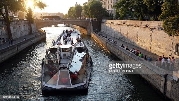 A tour boat travels on Seine river in Paris on July 29 next to the Notre Dame Cathedral AFP PHOTO / MIGUEL MEDINA