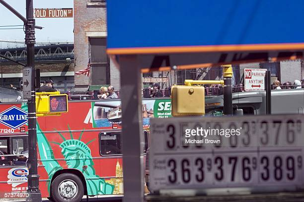 A tour bus passes full service gasoline prices for cash and credit card payment displayed at a Gulf gas station on Old Fulton Street April 20 2006 in...