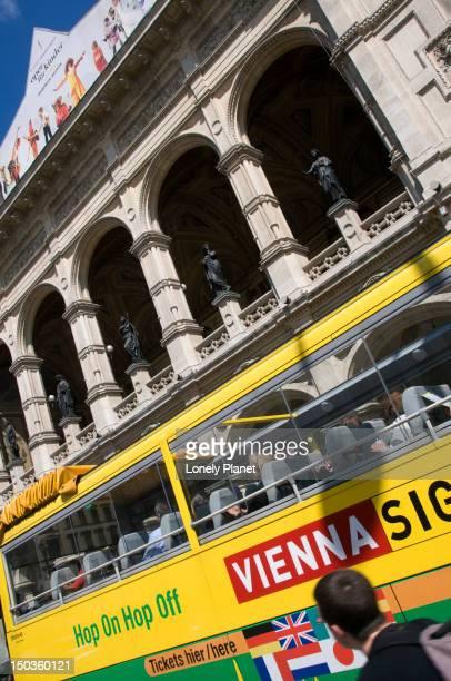 Tour bus passing Vienna Opera House.