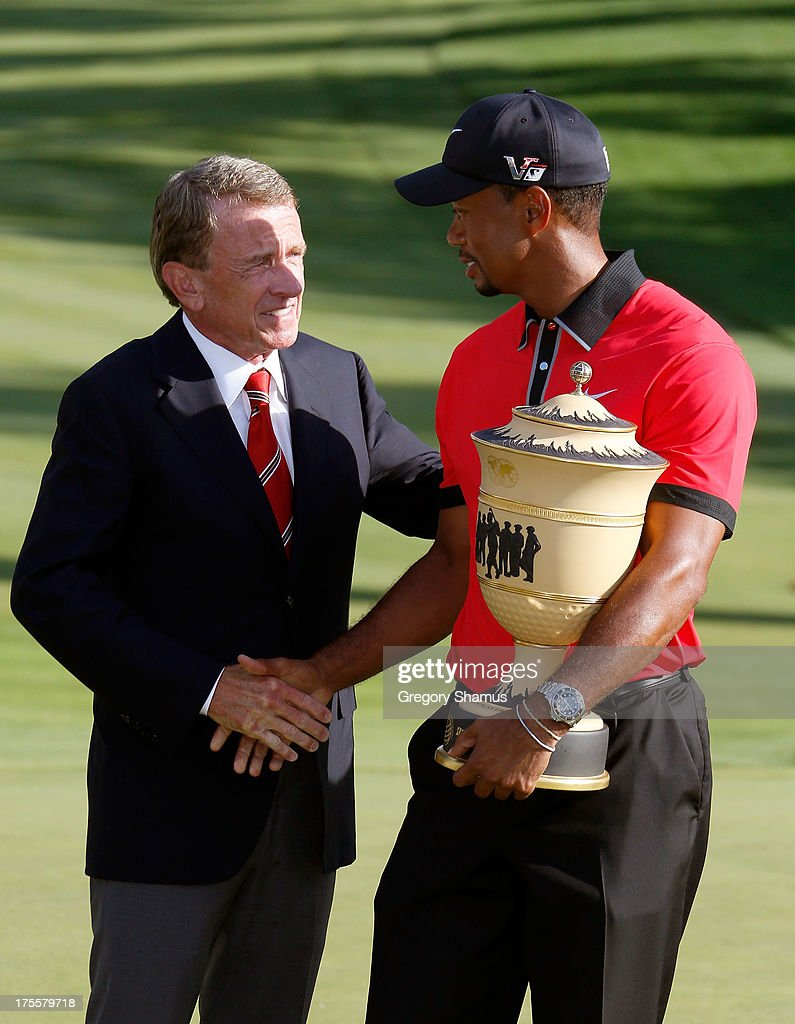 PGA Tour Commissioner Tim Finchem (L) shakes hands with Tiger Woods as he holds the Gary Player Cup trophy after the Final Round of the World Golf Championships-Bridgestone Invitational at Firestone Country Club South Course on August 4, 2013 in Akron, Ohio. Woods won the tournament with a score of -15.