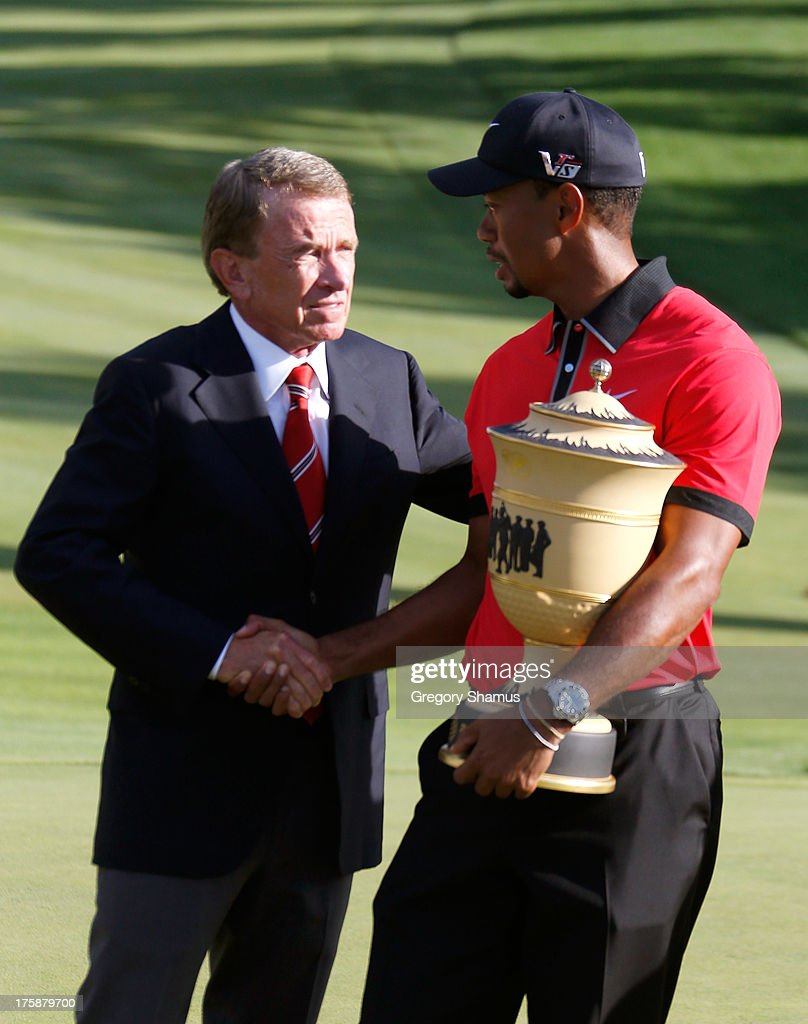 Tour Commissioner Tim Finchem (L) shakes hands with Tiger Woods as he holds the Gary Player Cup trophy after the Final Round of the World Golf Championships-Bridgestone Invitational at Firestone Country Club South Course on August 4, 2013 in Akron, Ohio. Woods won the tournament with a score of -15.