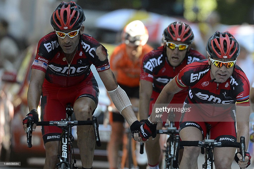 Tour de France 2011 winner, Australia's Cadel Evans (R) crosses the finish line with teammate, US George Hincapie (L) at the end of the197 km and sixteenth stage of the 2012 Tour de France cycling race starting in Pau and finishing in Bagneres de Luchon, southern France, on July 18, 2012.