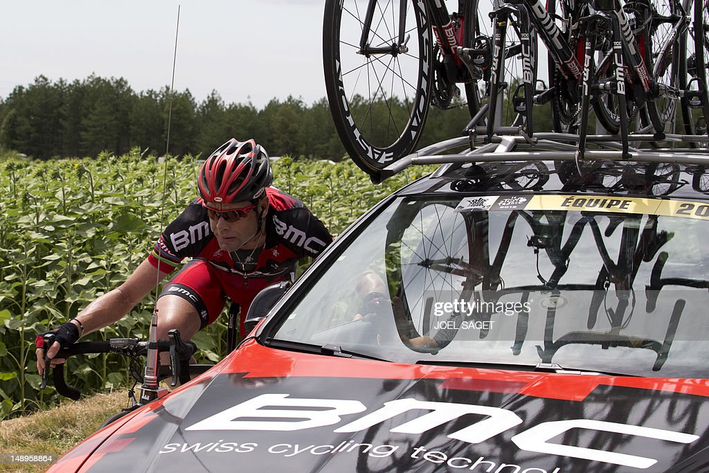 Tour de France 2011 winner, Australia's Cadel Evans speaks a team member as he rides next to his team car in the 222,5 km and eighteenth stage of the 2012 Tour de France cycling race starting in Blagnac and finishing in Brive-la-Gaillarde, southwestern France, on July 20, 2012. AFP PHOTO / JOEL SAGET