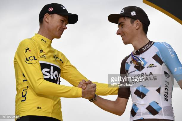 Tour de France 2017's winner Great Britain's Christopher Froome and France's Romain Bardet celebrate his overall leader yellow jersey on the podium...