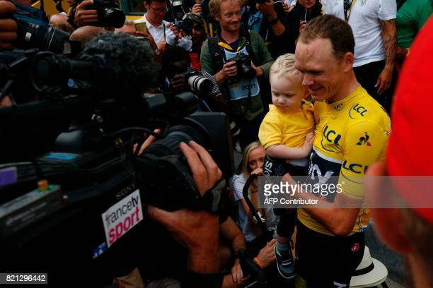 Tour de France 2017's winner Great Britain's Christopher Froome celebrates his overall leader yellow jersey poses with his baby Kellan at the end of...