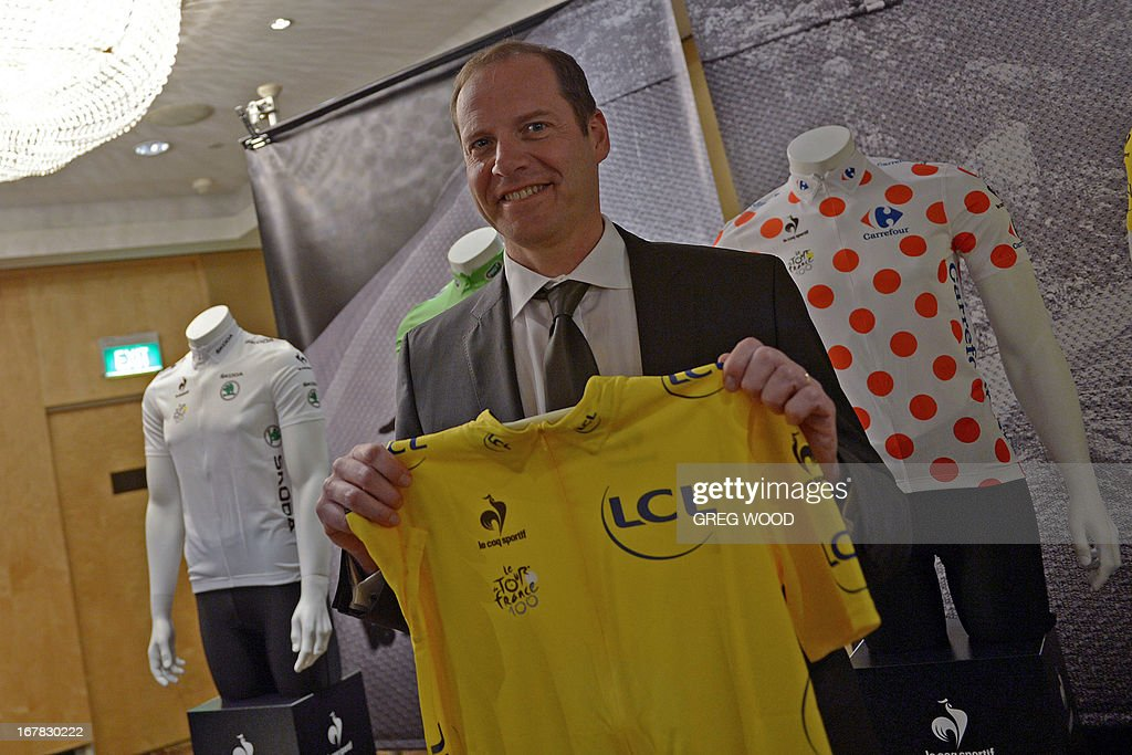 Tour de France boss Christian Prudhomme poses with a 100th edition le coq sportif yellow race jersey following a press conference held to promote the 100th running of the historic Tour de France cycling race in Sydney on May 1, 2013. Prudhomme on May 1 said the scandal-ridden sport of cycling had changed and is no longer 'the little ugly duckling' it is made out to be. The gruelling 21-stage 2013 event runs from June 29 to July 21.