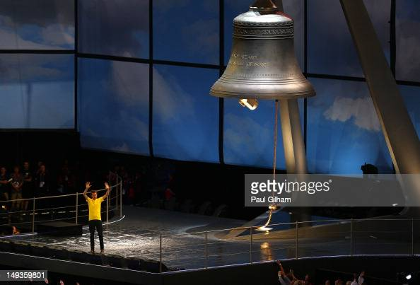 Tour de France champion Bradley Wiggins waves to the crowd after ringing a giant bell during the Opening Ceremony of the London 2012 Olympic Games at...