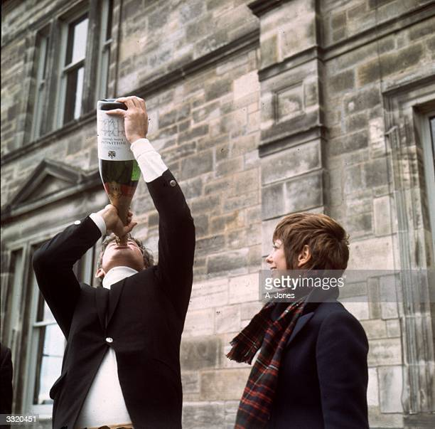 US tour golfer Doug Sanders drinking from a bottle of champagne at St Andrews Scotland beside his wife Scotty after the British Open Championship