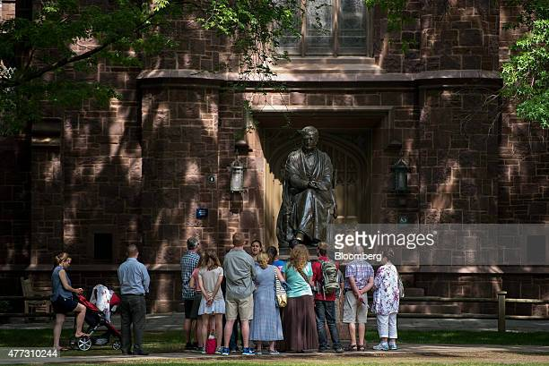 A tour group makes a stop at a statue of Theodore Woolsey on the Yale University campus in New Haven Connecticut US on Friday June 12 2015 Yale...