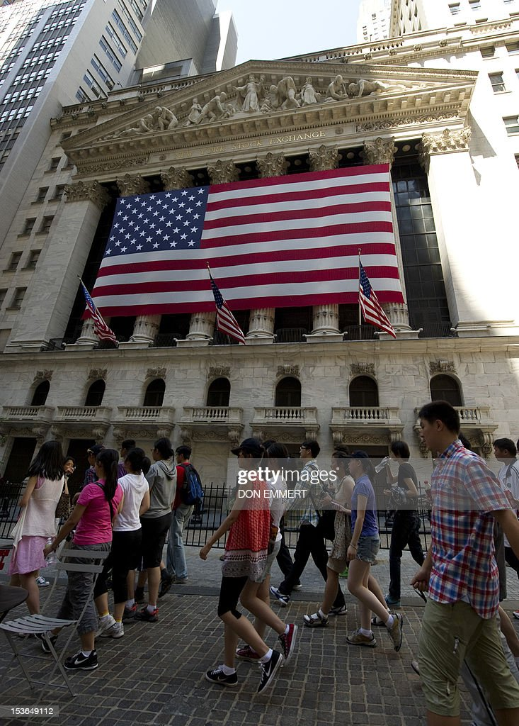 A tour group walks by the New York Stock Exchange August 3 2011 in New York World stock markets extended losses Wednesday as relief over a US debt...