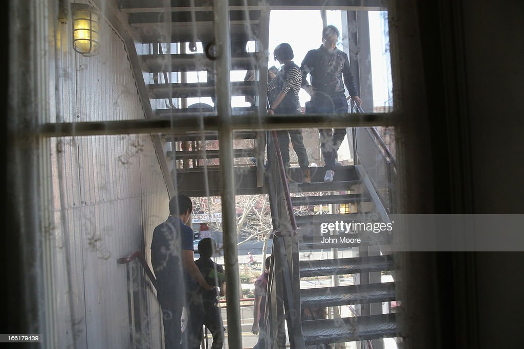 A tour group walks down the fire escape of the Lower East Side Tenement Museum on April 9, 2013 in New York City. The landmark museum preserves the history of more than 7,000 immigrants from more than 20 nations that lived, often in very cramped conditions, in the building between 1863 and 1935.
