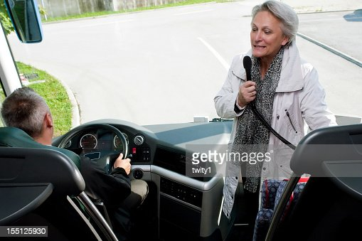 A tour guide entertaining tourists on a bus