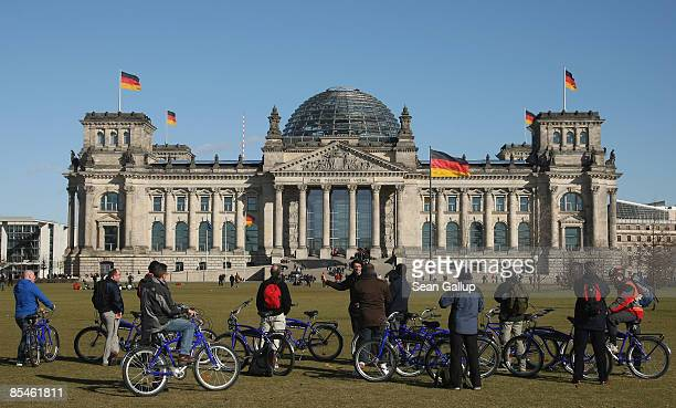 A tour guide explains German history of the 1930s to tourists on bicycles under blue skies in front of the Reichstag on March 17 2009 in Berlin...