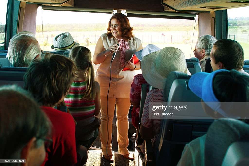 Tour guide holding microphone at front of coach full of tourists : Stock Photo