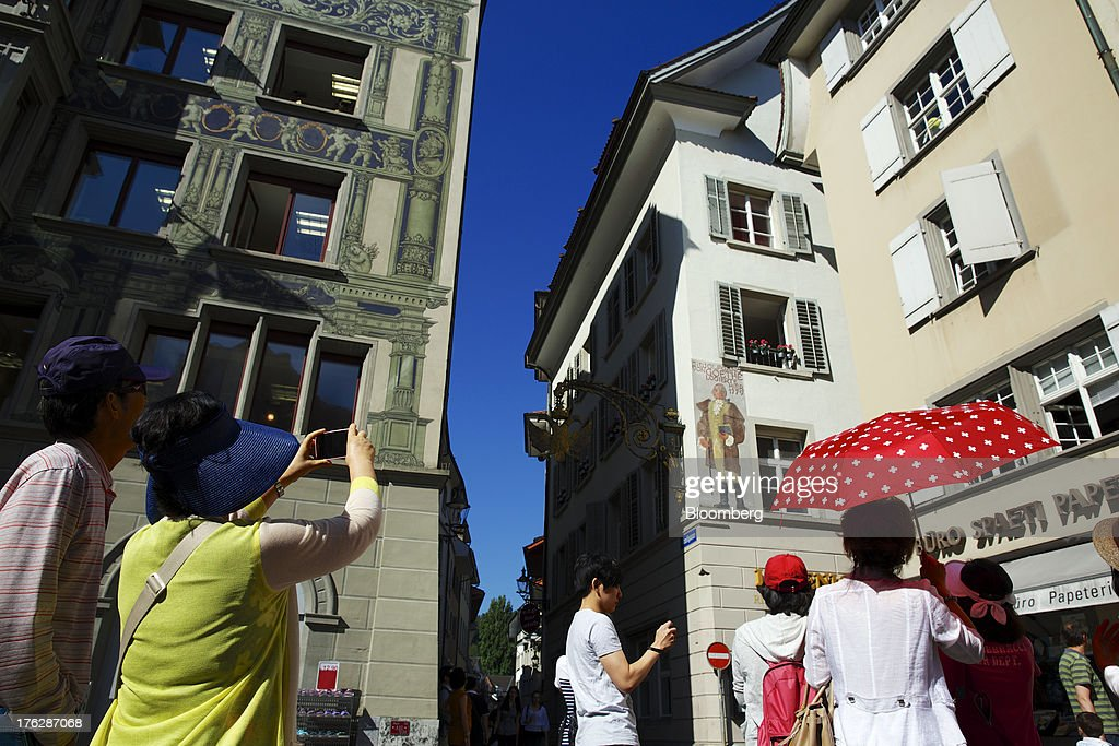 A tour guide holds a Swiss-themed umbrella as she walks with Asian tourists in Lucerne, Switzerland, on Saturday, Aug. 10, 2013. The Swiss National Bank will abolish its franc ceiling once it starts raising interest rates, Vice President Jean-Pierre Danthine said. Photographer: Gianluca Colla/Bloomberg via Getty Images