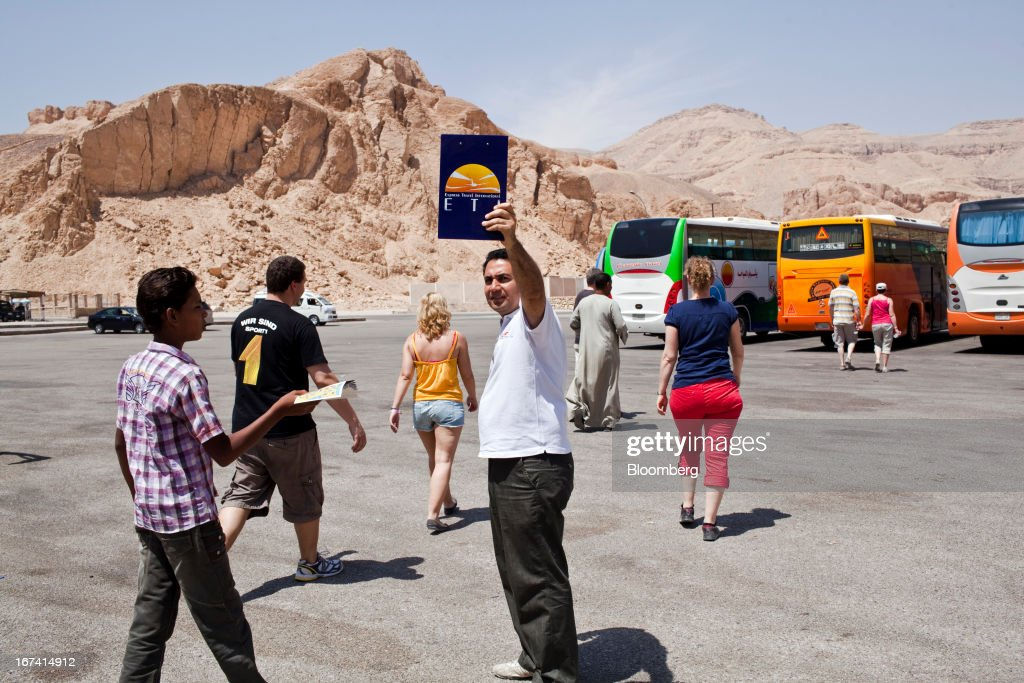 A tour guide raises his travel company card as he collects tourists in the coach park at the Valley of Kings in Luxor, Egypt, on Wednesday, April 24, 2013. Egypt ranked last in terms of security and safety on the World Economic Forum's 2013 Travel and Tourism Competitiveness Index. Photographer: Shawn Baldwin/Bloomberg via Getty Images
