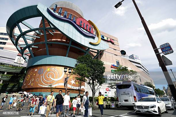 A tour guide right leads a group of Chinese tourists carrying shopping bags as they leave the Canal City Hakata commercial complex in Fukuoka Japan...