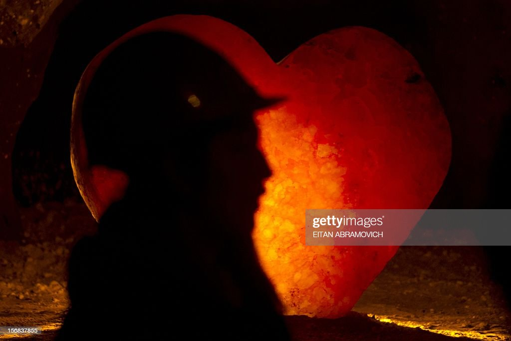 A tour guide stands in front of a salt crystal weighing 1,600 kg, carved into the shape of a heart at Nemocon's salt mine in Nemocon, Cundinamarca, Colombia on November 22, 2012. The mine, an impressive construction at 80 meters of depth with over 500 years of history, has become a new attractive tourist destination in Colombia. AFP PHOTO/Eitan Abramovich