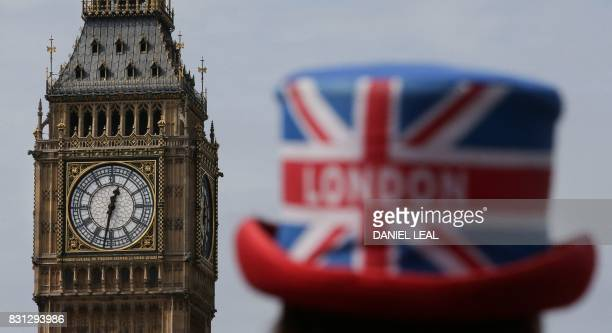A tour guide wearing a Union Flag and Londonthemed hat stands near one of the four faces of the Great Clock of the Elizabeth Tower commonly referred...