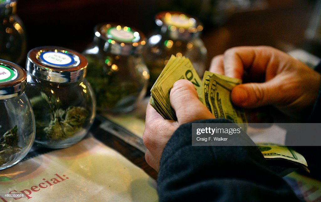 A tour members purchases marijuana at La Conte's Clone Bar Dispensary during a marijuana tour hosted by My 420 Tours in Denver CO on December 06 2014...