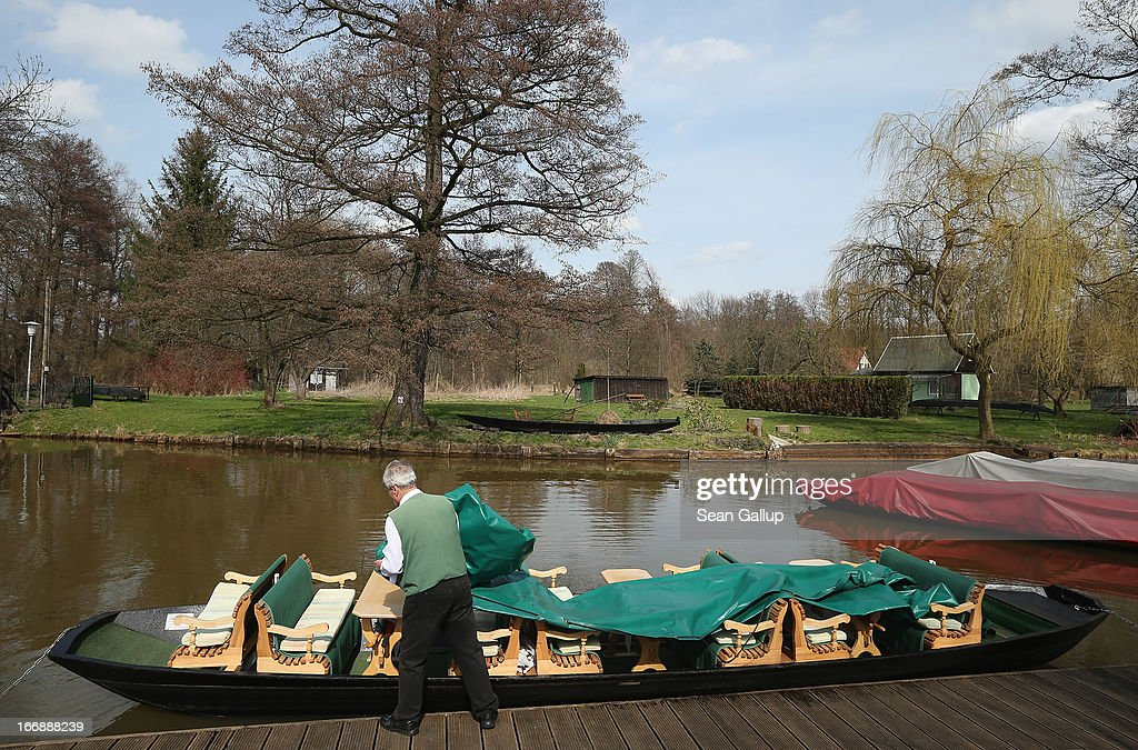 A tour operator covers a flat-bed canoe called a Kahn used for ferrying visitors along one of the many canals in the Spreewald region on April 17, 2013 near Luebbenau, Germany. The nearby Wudritz creek is heavily burdened with iron from the nearby former Schlabendorf open pit coal mine, which has since been turned into a lake called the Schlabendorfer See. Many creeks and small rivers that feed the Spree River have turned a rich orange or brown, sometimes even red, due to the sediments flowing from several former open pit coal mines. The Spreewald is a popular tourist destination known for its network of canals and local tour operators fear the sediment will turn the waters there orange as well, which could seriously impact the tourist seasons. Though the iron sediment is not poisonous, some local farmers claim they have been forced to filter the water they use to irrigate their fields, and many people report the disappearance of fish and other fauna.