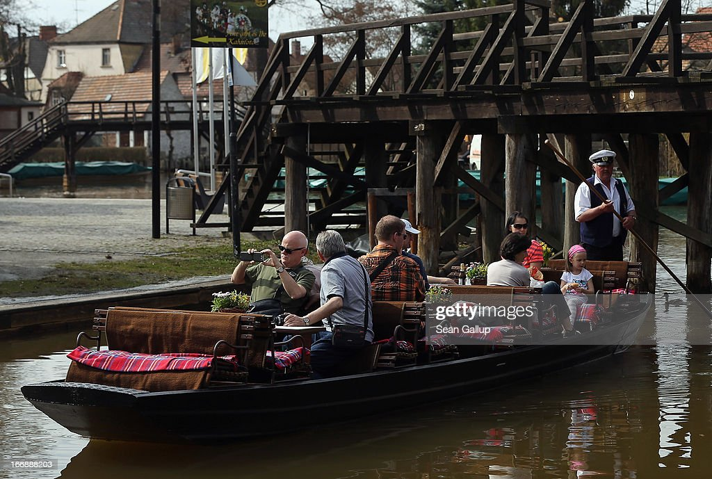 A tour operator ferries visitors in a flat-bed canoe called a Kahn along one of the many canals on the Spreewald region on April 17, 2013 near Luebbenau, Germany. The nearby Wudritz creek is heavily burdened with iron from the nearby former Schlabendorf open pit coal mine, which has since been turned into a lake called the Schlabendorfer See. Many creeks and small rivers that feed the Spree River have turned a rich orange or brown, sometimes even red, due to the sediments flowing from several former open pit coal mines. The Spreewald is a popular tourist destination known for its network of canals and local tour operators fear the sediment will turn the waters there orange as well, which could seriously impact the tourist seasons. Though the iron sediment is not poisonous, some local farmers claim they have been forced to filter the water they use to irrigate their fields, and many people report the disappearance of fish and other fauna.