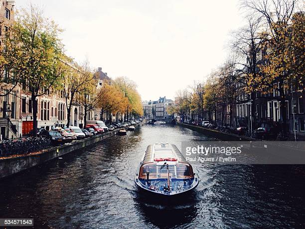 Tourboat Going Along Urban Canal