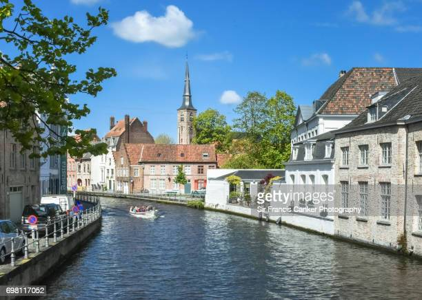 Tourboat with unrecognizable tourists along picturesque 'Sint-Annarei' canal in Bruges, Flanders, Belgium